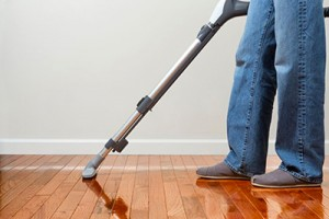 Man Vacuuming Wood Floor